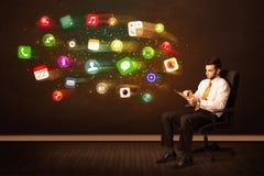 Бизнесмен сидя в стуле офиса с таблеткой и красочным ap Стоковые Фотографии RF