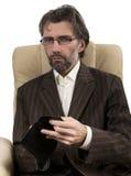 Бизнесмен сидя в стуле с бумажником Стоковая Фотография