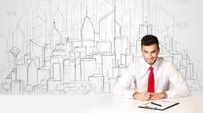 Бизнесмен сидя на белой таблице с зданиями нарисованными рукой Стоковая Фотография
