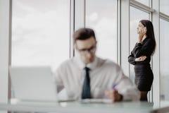 Бизнесмен сидя на столе в офисе используя компьтер-книжку, пока женщины говоря телефон на заднем плане Стоковая Фотография RF