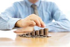 Бизнесмен сидя на столе и монетках Стоковая Фотография