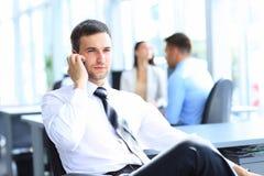 Бизнесмен сидит на его столе пока говорящ на черни в офисе