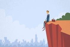 Бизнесмен сидя верхняя гора утеса скалы Стоковое фото RF