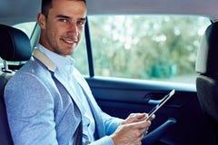 Бизнесмен сидя в автомобиле с планшетом Стоковая Фотография