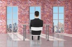 Бизнесмен сидя в комнате кирпича Стоковые Изображения RF