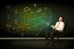 Бизнесмен сидя в стуле держа таблетку с значками средств массовой информации Стоковые Изображения RF