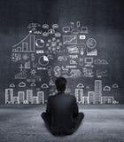 Бизнесмен сидя и смотря к бизнес-плану Стоковое Изображение