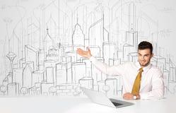 Бизнесмен сидя на белой таблице с зданиями нарисованными рукой Стоковые Изображения