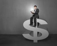Бизнесмен сидя на верхней части символа денег с таблеткой и l Стоковое Фото
