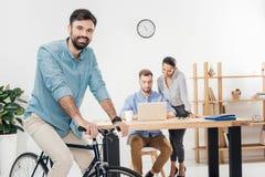 Бизнесмен сидя на велосипеде пока коллеги работая на компьтер-книжке в офисе Стоковое Изображение RF