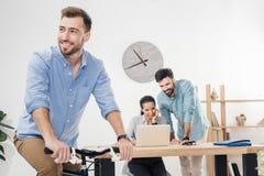 Бизнесмен сидя на велосипеде пока коллеги работая на компьтер-книжке в офисе Стоковые Изображения