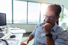 Бизнесмен сидя на его столе в офисе Стоковые Фотографии RF