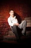 бизнесмен сидя на лестницах приближает к кирпичной стене Стоковое фото RF