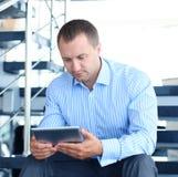 Бизнесмен сидя на лестницах Стоковые Фото