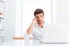 Бизнесмен сидя на рабочем месте и говоря на мобильном телефоне Стоковые Изображения RF
