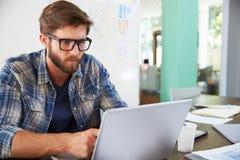Бизнесмен сидя на столе в офисе работая на компьтер-книжке Стоковая Фотография RF