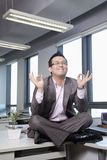 Бизнесмен сидя на столе в размышлять офиса стоковые изображения
