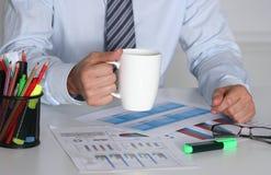 Бизнесмен сидя на столе офиса имея перерыв на чашку кофе и держа кружку Стоковые Изображения RF