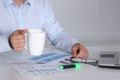 Бизнесмен сидя на столе офиса имея перерыв на чашку кофе и держа кружку Стоковая Фотография