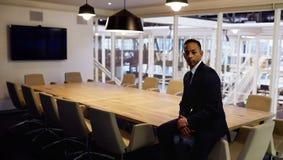 Бизнесмен сидя на столе переговоров самостоятельно в пустом офисе Стоковая Фотография