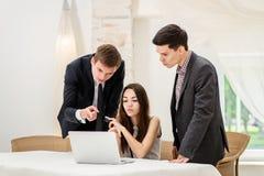 Бизнесмен 3 сидя на таблице и сидит и наблюдает работа Стоковые Изображения RF