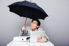 Бизнесмен сидя на таблице с компьтер-книжкой и держа umbrell Стоковая Фотография RF