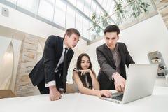 Бизнесмен 3 сидя на таблице Стоковые Изображения