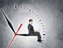 Бизнесмен сидя на clockhand Стоковое фото RF