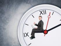 Бизнесмен сидя на clockhand Стоковое Изображение