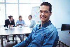 Бизнесмен сидя против коллег в конференц-зале Стоковое Фото