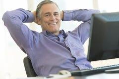 Бизнесмен сидя с руками за головой на столе офиса стоковые фотографии rf