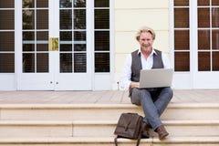 Бизнесмен сидя outdoors на шагах с компьтер-книжкой Стоковое Изображение RF