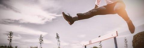 Бизнесмен скача барьер пока бегущ стоковое изображение rf