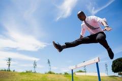 Бизнесмен скача барьер пока бегущ стоковые фотографии rf