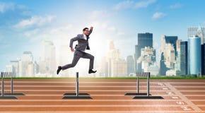 Бизнесмен скача над барьерами в концепции дела Стоковое фото RF