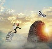 Бизнесмен скача на весну для достижения флага Цель бизнеса достижения и трудная концепция карьеры стоковые фотографии rf