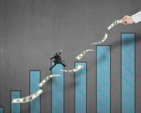 Бизнесмен скача на деньги с владением одним руки и диаграммой Стоковые Фотографии RF