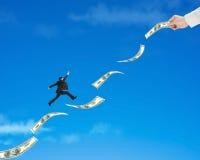 Бизнесмен скача на деньги с владением одним руки Стоковая Фотография