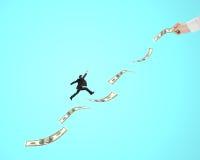 Бизнесмен скача на деньги с другим владением одним человека Стоковое Изображение RF