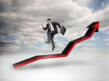 Бизнесмен скача над красной стрелкой указывая вверх стоковая фотография rf