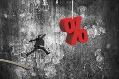 Бизнесмен скача от деревянной доски к красному знаку процента Стоковая Фотография RF