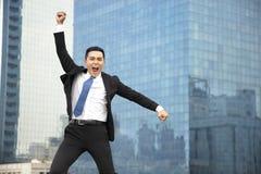 бизнесмен скача с предпосылкой городского пейзажа стоковые фото