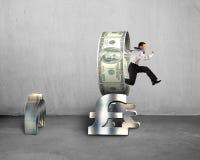 Бизнесмен скача через круг на символах денег стога Стоковое фото RF