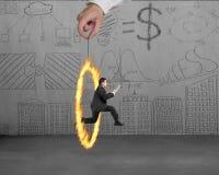 Бизнесмен скача через руку круга огня держа с doodle Стоковое Изображение RF