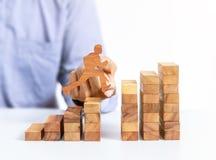Бизнесмен скачет через зазор на деревянном блоке стоковые изображения