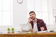 Бизнесмен сконцентрированный детенышами прочитал документы в современном белом офисе Стоковые Изображения RF