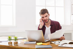 Бизнесмен сконцентрированный детенышами прочитал документы в современном белом офисе Стоковое Фото