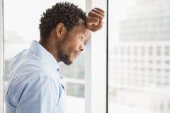 Бизнесмен сконцентрированный детенышами смотря из окна Стоковая Фотография