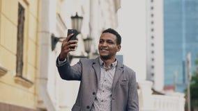 Бизнесмен смешанной гонки имея онлайн видео- болтовню в бизнес-конференции используя smartphone Стоковое Изображение RF