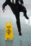 Бизнесмен смещая на влажный пол Стоковая Фотография